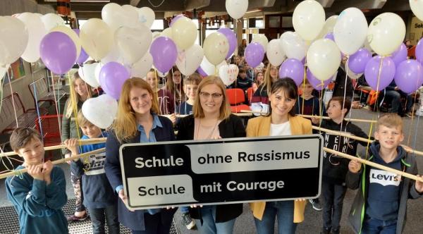 Die Lehrerinnen Felicitas Trienekens, Stacey Naumann und Julia Schlieper (v.l.) zeigen das Schild. Es wird im PZ aufgehängt.